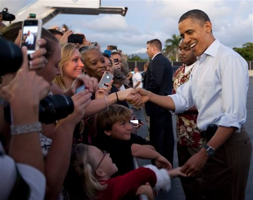 President Barack Obama shakes hands with people waiting to greet him on the tarmac as he steps off of Air Force One at Hickam Air Force Base in Friday, Dec. 23, 2011, in Honolulu. (AP Photo/Carolyn Kaster)