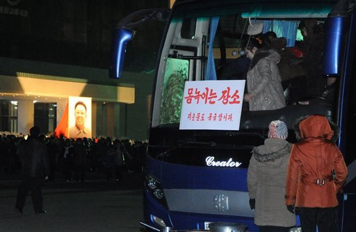 Mourners use a bus to stay warm as many gather around a portrait of the late leader Kim Jong Il hanging outside the Pyongyang Circus Theater in Pyongyang, North Korea on Saturday, Dec. 24, 2011. (AP Photo)