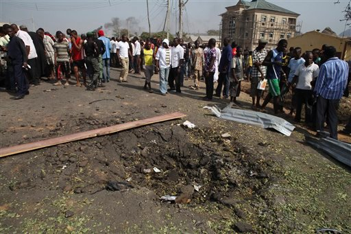 Onlookers gather around crater following a bomb blast at St. Theresa Catholic Church in Madalla, Nigeria, Sunday, Dec. 25, 2011. (AP Photo/Sunday Aghaeze)