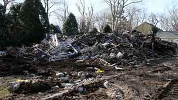 Rubble left after the demolition of a house where a fire left five people dead Christmas Day lies on the ground, Monday, Dec. 26, 2011, in Stamford, Conn. (AP Photo/Tina Fineberg)