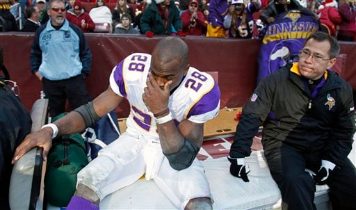 Minnesota Vikings running back Adrian Peterson (28) reacts as he's driven off the field after an injury during the second half of an NFL football game against Washington Redskins in Landover, Md., Saturday, Dec. 24, 2011. (AP Photo/Evan Vucci)