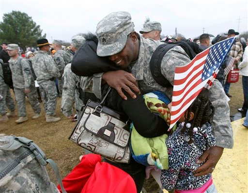 FILE - In this Dec. 24, 2011 file photo, Sgt. Howard Acoff hugs his family as U.S. Army 1st Cavalry 3rd Brigade soldiers return home from deployment in Iraq at Fort Hood, Texas. (AP Photo/Erich Schlegel, File)