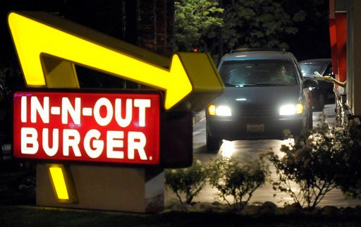 FILE - In this June 8, 2010, file photo, a customer receives an order from the drive-through at an In-N-Out Burger. (AP Photo/Adam Lau, File)