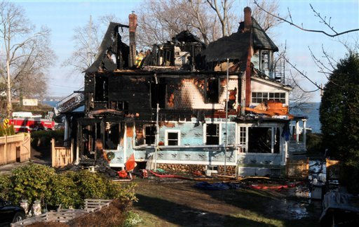 FILE - In this Dec. 25, 2011 file photo, firefighters investigate a house in Stamford, Conn., where an early morning fire left five people dead. (AP Photo/Tina Fineberg, File)