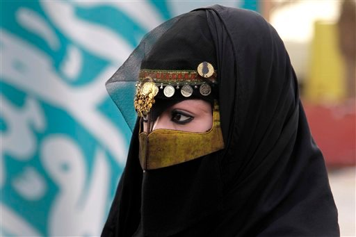 FILE - In this Friday, April 29, 2011 file photo, a Saudi woman attends a traditional Arda dance, or War dance, during the Janadriyah Festival of Heritage and Culture, on the outskirts of the Saudi capital Riyadh, Saudi Arabia.