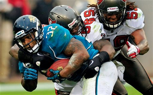 FILE - In this Dec. 11, 2011 file photo, Jacksonville Jaguars running back Maurice Jones-Drew (32) is tackled by Tampa Bay Buccaneers outside linebacker Quincy Black (58) and middle linebacker Mason Foster (59) during the second half of an NFL game.
