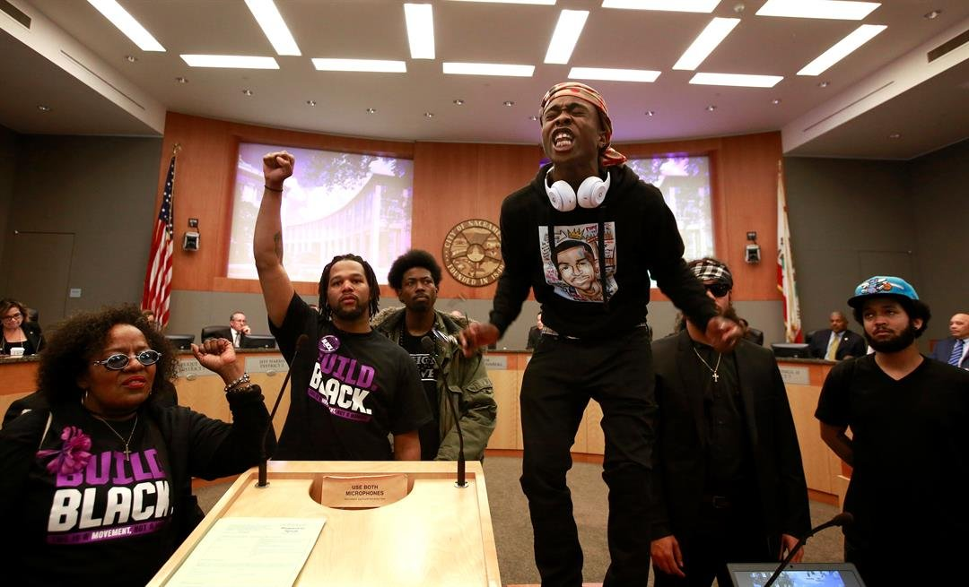 Stevante Clark stands on a desk and shouts the name of his brother Stephon Clark, who was fatally shot by police. Stevante Clark disrupted the meeting demanding to speak, causing the city council to adjourn for a 15-minute recess. (AP Photo/Rich Pedroncel