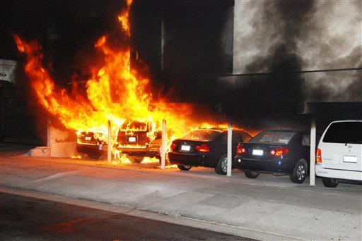 Burning cars are shown at the site of an arson fire in the Hollywood section of Los Angeles on Friday Dec.30, 2011. (AP Photo/Mike Meadows)