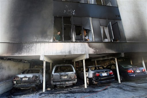 An investigator works the scene where fire caused damage to a two-story apartment at 1156 N. Cahuenga Blvd. in Hollywood, section of Los Angeles, on Friday, Dec. 30, 2011. (AP Photo/Ringo H.W. Chiu)