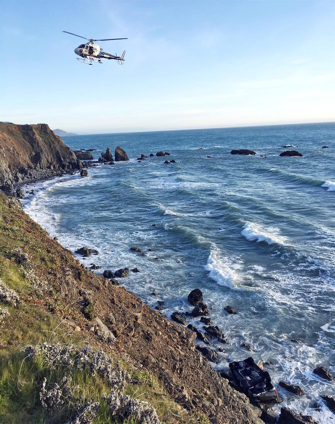 A helicopter hovering over steep coastal cliffs near Mendocino, Calif., where a vehicle, visible at lower right, plunged about 100 feet off a cliff along Highway 1, killing all five passengers. (California Highway Patrol via AP)