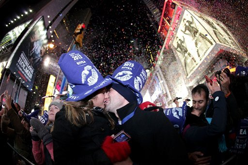 Kelsey Harpin, 21, left, and Joe Courcy, 22, both from Boston, share a midnight kiss during the New Year's celebration at Times Square, Sunday, Jan. 1, 2012, in New York. (AP Photo/Julio Cortez)