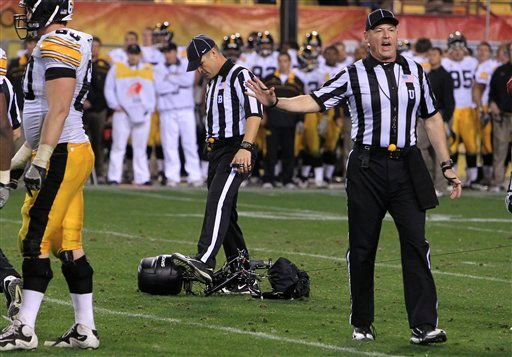 Umpire Tim Schroeder, right, keeps players away as back judge William Robinson kicks a network overhead television camera after it crashed to the field during the fourth quarter in the Insight Bowl NCAA college football game Friday, Dec. 30, 2011 (AP)