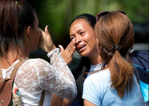 Relatives cry after learning their loved ones died in a fast-moving fire a day prior that swept through a police station where prisoners were being kept in crowded cells, in Valencia, Venezuela, Thursday, March 29, 2018.