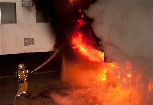 A Los Angeles Fire Department firefighter extinguishes multiple cars on fire in a carport in the Sun Valley neighborhood of Los Angeles on Saturday, Dec. 31, 2011. (AP Photo/Dan Steinberg)