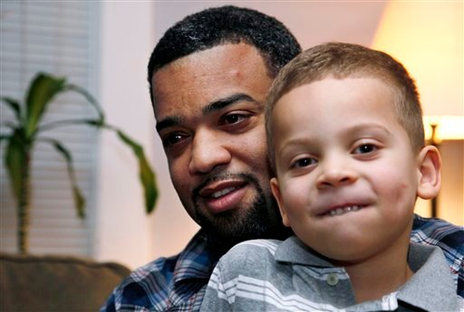 In this Dec. 27, 2011 photo, Damon Brown sits with his son Julian, 5, at their home in Seattle. Damon Brown found a kidney on Facebook after telling his story on a special page. (AP Photo/Elaine Thompson)