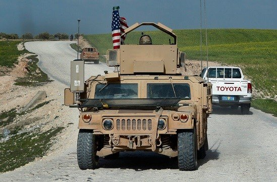 In this picture taken on Thursday, March 29, 2018, U.S. troop's humvee passes vehicles of fighters from the U.S-backed Syrian Manbij Military Council.