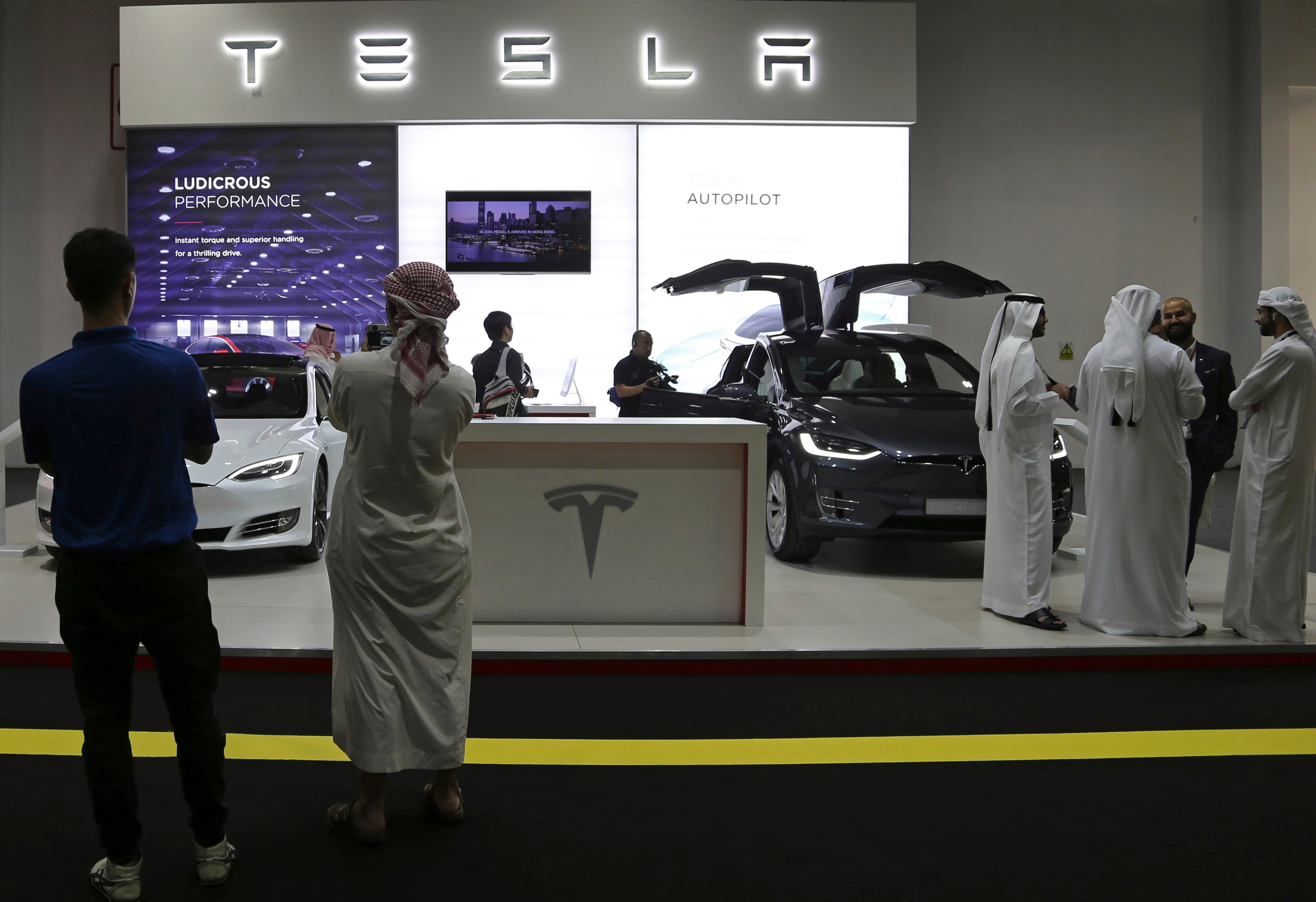 People visit the Tesla stand at the Dubai Motor Show in the United Arab Emirates, Tuesday, Nov. 14, 2017.