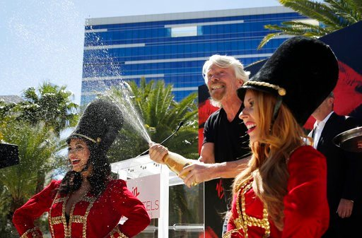 Virgin Group founder Richard Branson sprays champagne at a news conference Friday, March 30, 2018, in Las Vegas where Virgin Hotels announced that it had bought the Hard Rock hotel and casino in Las Vegas. (AP Photo/John Locher)
