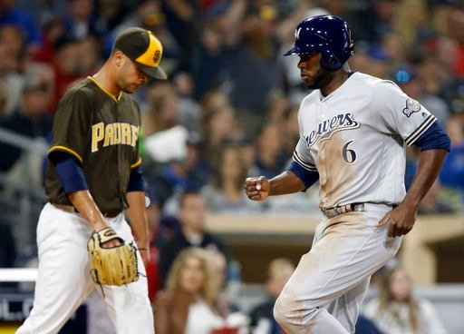 Milwaukee Brewers' Lorenzo Cain, right, scores in front of San Diego Padres starting pitcher Joey Lucchesi on a sacrifice fly hit by Ryan Braun during the fifth inning of a baseball game in San Diego, Friday, March 30, 2018. (AP Photo/Alex Gallardo)