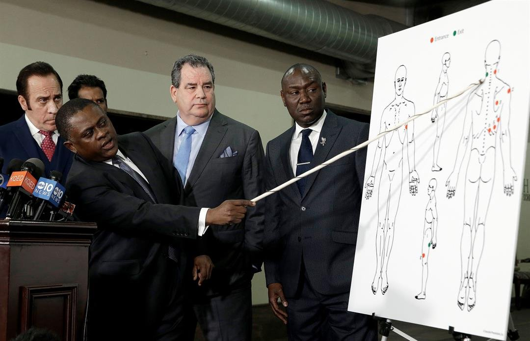 Pathologist, Dr. Bennet Omalu, second from left, gestures to a diagram showing where police shooting victim Stephon Clark was struck by bullets, during a news conference, Friday, March 30, 2018 (AP Photo/Rich Pedroncelli)