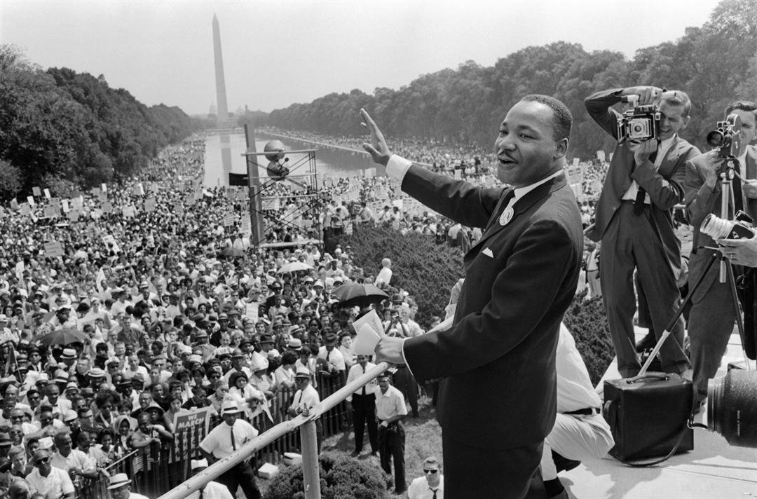 The civil rights leader Martin Luther KIng (C) waves to supporters 28 August 1963 on the Mall in Washington DC (Washington Monument in background) during the 'March on Washington'.