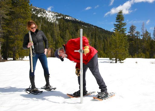 Frank Gehrke, chief of the California Cooperative Snow Surveys Program for the Department of Water Resources, checks the depth of the snowpack as Karla Nemeth, director of DWR, looks on during the snow survey, Monday, April 2, 2018, near Echo Summit, Cali
