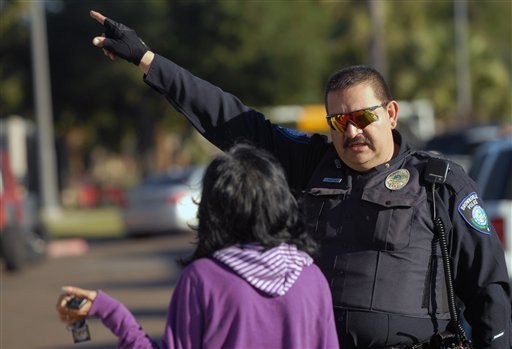 A Brownsville Police officer directs a parent to a building at Dean Porter Park in Brownsville,Texas, Wednesday, Jan. 4,2012. (AP Photo/The Brownsville Herald, Brad Doherty)