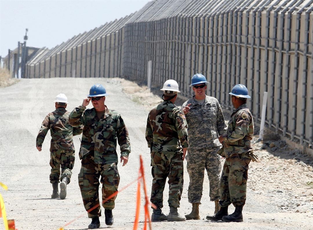 ** FILE ** Members of the California National Guard work next to the U.S.-Mexico border fence Wednesday, June 21, 2006, before a news conference by CA Gov. Arnold Schwarzenegger near the San Ysidro Port of Entry in San Diego. (AP Photo/Denis Poroy)