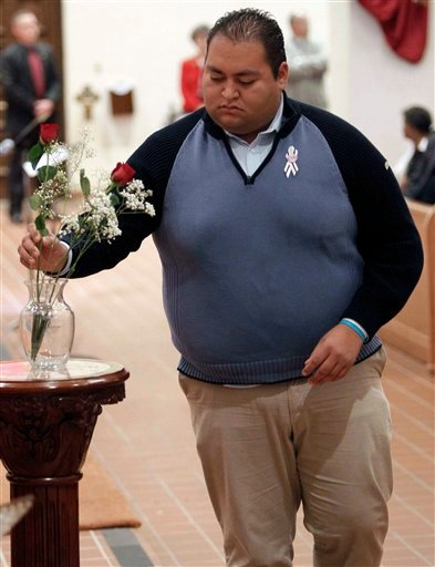Daniel Hernandez leaves one of six roses for the six people killed in the shooting at an event for U.S. Rep. Gabrielle Giffords one year ago, during an interfaith remembrance service at St. Augustine Catherdral, Sunday, Jan. 8, 2012 in Tucson, Ariz. (AP)