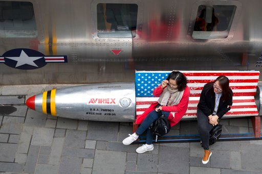 In this Friday, March 23, 2018, file photo, Chinese women sit on a bench with a U.S. flag theme outside an apparel store in Beijing.