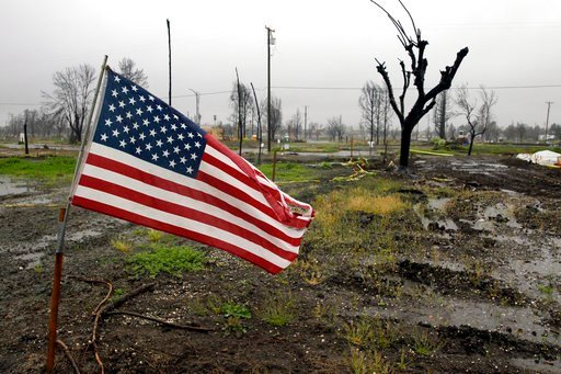 A U.S. Flag is placed on a wildfire-ravaged property as rain comes down in the the Coffey Park area Friday, April 6, 2018, in Santa Rosa, Calif.