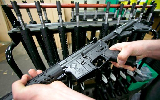 FILE - In this April 10, 2013 file photo, craftsman Veetek Witkowski holds a newly assembled AR-15 rifle at the Stag Arms company in New Britain, Conn. (AP Photo/Charles Krupa, File)