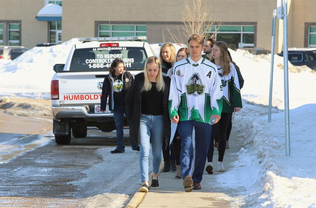 People, including a young man wearing a Humboldt Broncos jersey, approach the Uniplex April 8, 2018 in Humboldt, Canada, prior to a memorial vigil for the Humboldt Broncos ice hockey team.