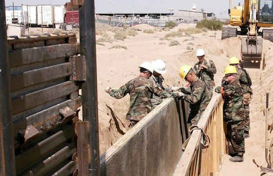 FILE - In this June 5, 2006, file photo, Utah National Guard troops from the 116th Construction Equipment Support Company prepare to extend a wall along the U.S. border in San Luis, Ariz.