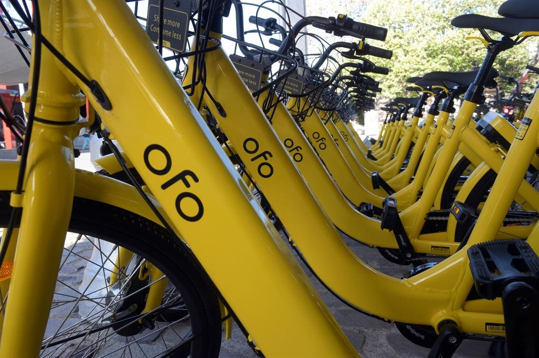 A picture taken on October 20, 2017 shows Chinese station-free bikes sharing platform OFO Bicycles at the 'Autonomy and the urban mobility' fair in Paris on October 20, 2017.