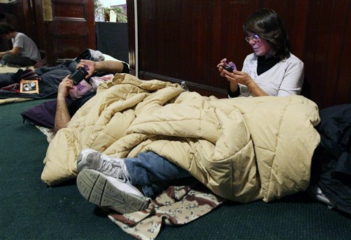 Donna Marinelli, of New Britain, Conn., foreground, and her cousin David Monarca, use their phones as they spend the night in a church space being funded by Occupy Wall Street for Occupy Wall Street protestors. (AP Photo/Tina Fineberg)