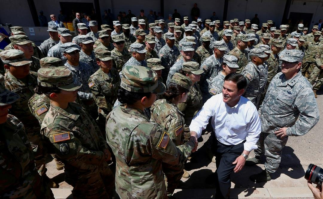 Arizona's Republican Gov. Doug Ducey, front right, meets with Arizona National Guard soldiers prior to their deployment to the Mexico border at the Papago Park Military Reservation on Monday, April 9, 2018.