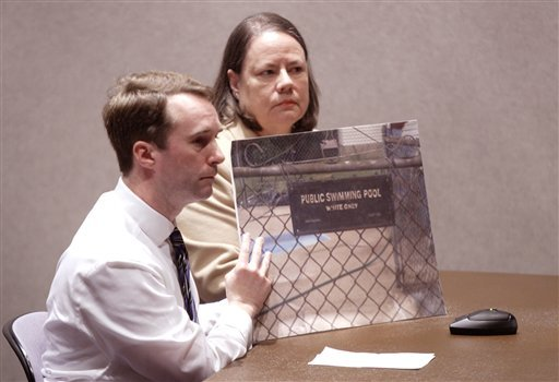 Michael Gunn, left, of Cincinnati holds a picture of a sign that his landlord, Jamie Hein, posted on the entrance of the apartment swimming pool as Elizabeth Brown, executive director of Housing Opportunities Made Equal, looks on. (AP Photo/Paul Vernon)