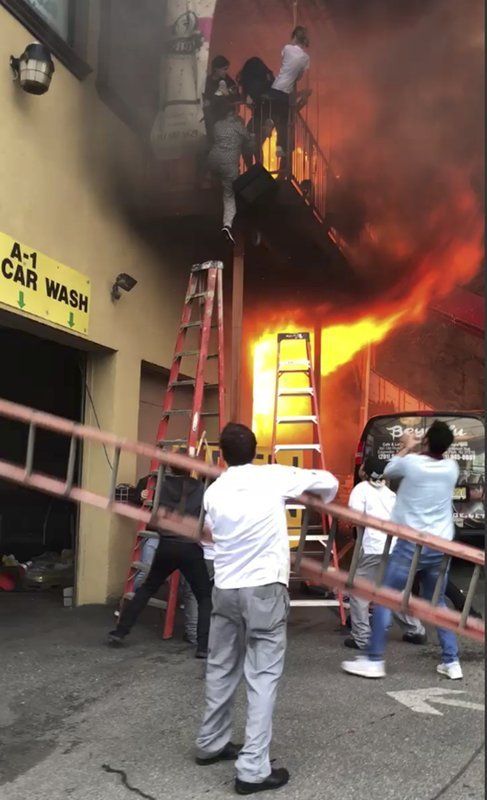 In this Monday, April 9, 2018 photo, girls flee a second-story dance studio onto a balcony as a roaring fire engulfs their building in Edgewater, N.J.