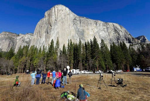 FILE - In this Jan. 14, 2015, file photo, spectators gaze at El Capitan for a glimpse of climbers Tommy Caldwell and Kevin Jorgeson, as seen from the valley floor in Yosemite National Park, Calif. The Interior Department is backing down from a plan to imp