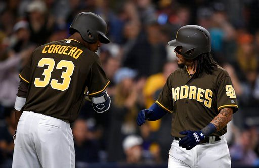 San Diego Padres' Freddy Galvis, right, celebrates with Franchy Cordero after scoring off an RBI single by Tyson Ross during the fifth inning of a baseball game against the San Francisco Giants in San Diego, Friday, April 13, 2018. (AP Photo/Kelvin Kuo)