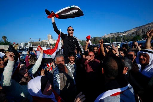 Hundreds of Syrians are demonstrating in a landmark square in the Syrian capital, waving victory signs and honking their car horns in a show of defiance. (AP Photo/Hassan Ammar)