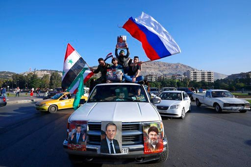 Syrian government supporters wave Syrian, Iranian and Russian flags as they chant slogans against U.S. President Trump during demonstrations following a wave of U.S., British and French military strikes to punish President Bashar Assad for suspected chemi