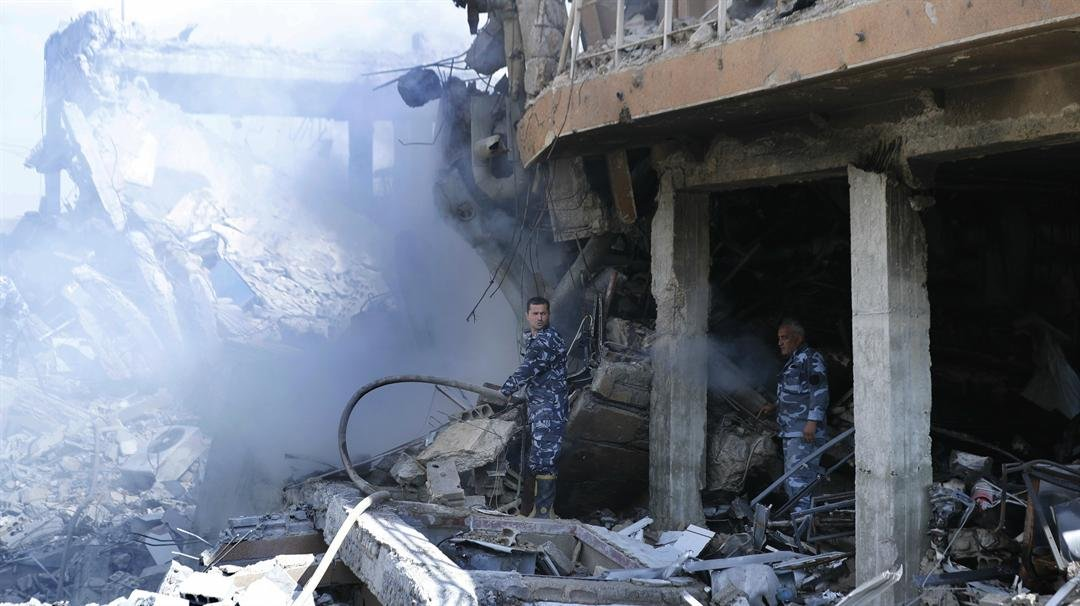 Firefighters extinguish smoke from the damage of the Syrian Scientific Research Center which was attacked by U.S., British and French military strikes to punish President Bashar Assad for suspected chemical attacks against civilians. (AP/Hassan Ammar)