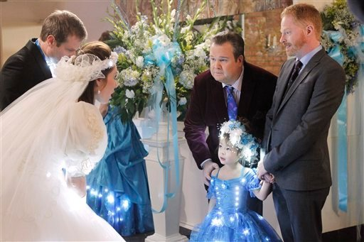 In this image released by ABC, from right, Jesse Tyler Ferguson portraying Mitchell Pritchett, and Eric Stonestreet portraying Cameron Tucker are shown with Aubrey Anderson-Emmons, who plays their adopted daughter Lily in a scene from Modern Family.