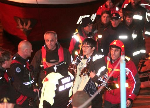 FILE - In this Sunday, Jan. 15, 2012 file photo, a passenger from South Korea, center, walks with Italian firefighters after being rescued from the luxury cruise ship Costa Concordia which ran aground on the small Tuscan island of Giglio, Italy.