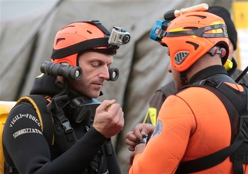 Italian divers chat as they prepare to head out to the cruise ship Costa Concordia, as it lays on its side after running aground off the tiny Tuscan island of Giglio, Italy, Jan. 19, 2012. (AP Photo/Gregorio Borgia)