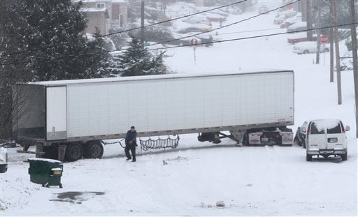 A man walks past a truck stuck in the snow on 22 Avenue S. at S. Hill Street in Seattle, Wednesday. Jan. 18, 2012, (AP Photo/The Seattle Times, Ken Lambert)