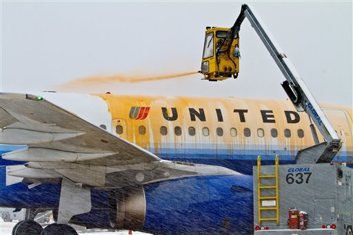 Ground crews spray de-icer onto a United Airlines jet ready for take-off at Seattle-Tacoma International Airport on Jan. 18, 2012. Airport crews worked 12-hour shifts keeping the runways clear of snow. (AP Photo/The Seattle Times, Mike Siegel)