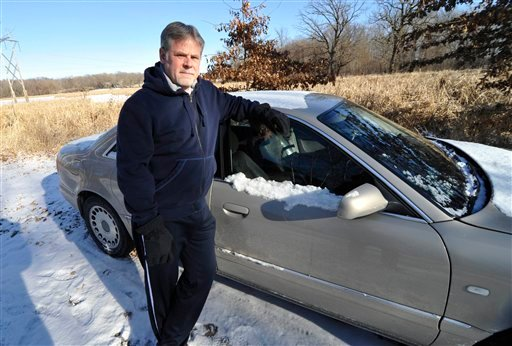 Chris Jenks, 54, who became homeless in his hometown of Minneapolis-St. Paul after a successful career in sales and marketing, is shown outside a friends' home beside the car he lived in for a time on Thursday, Jan. 19, 2012, in Rogers, Minn.